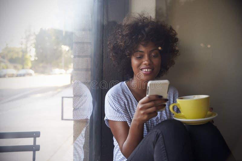 Młoda murzynka używa smartphone obok okno w kawiarni zdjęcie royalty free