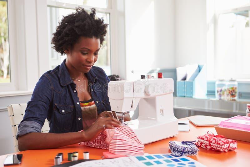 Młoda murzynki zaszywania tkanina używać szwalną maszynę zdjęcie royalty free