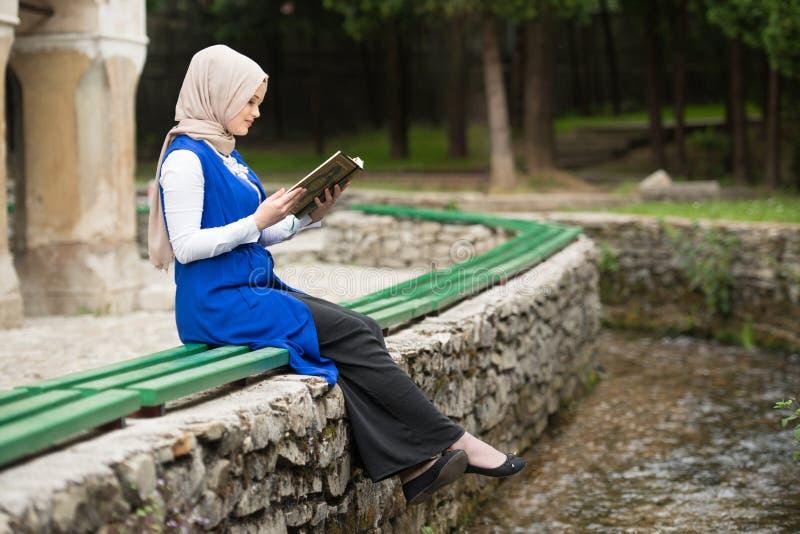 Młoda Muzułmańska kobieta Czyta Świętego Islamskiego Książkowego Koran obrazy stock