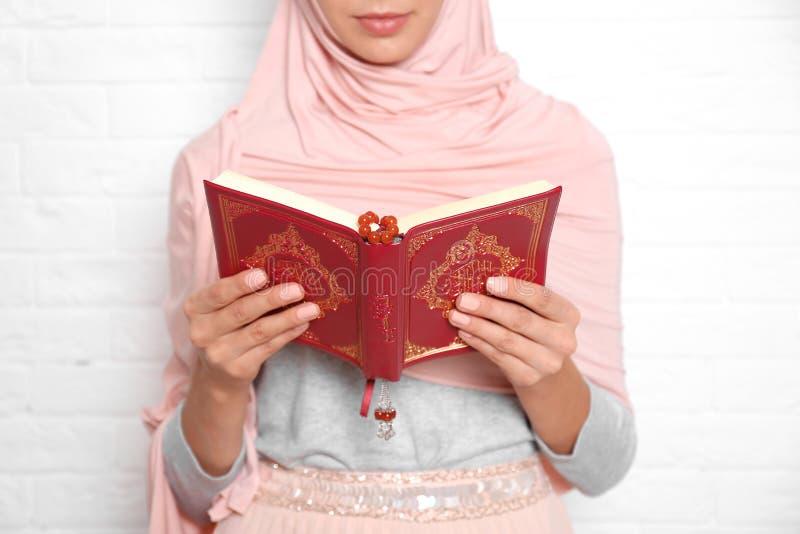 Młoda Muzułmańska kobieta czyta Koran przeciw ścianie z cegieł obraz stock