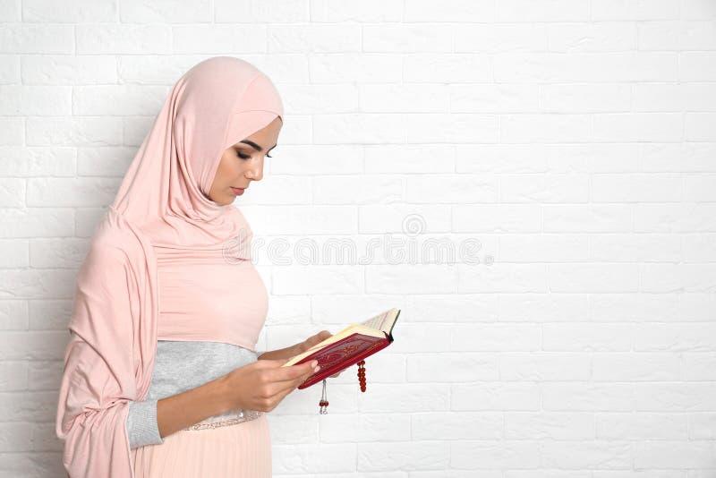 Młoda Muzułmańska kobieta czyta Koran w hijab obrazy royalty free