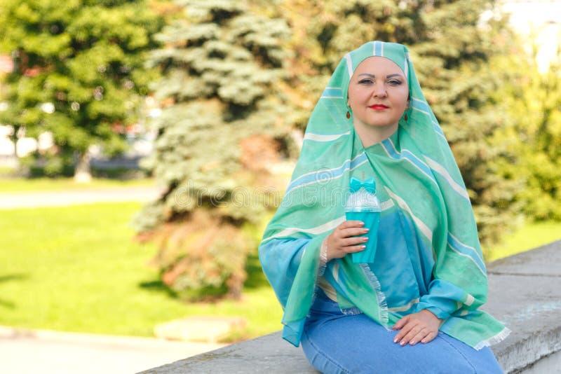 Młoda Muzułmańska kobieta w lekkim szaliku w parku pije kawę zdjęcia stock