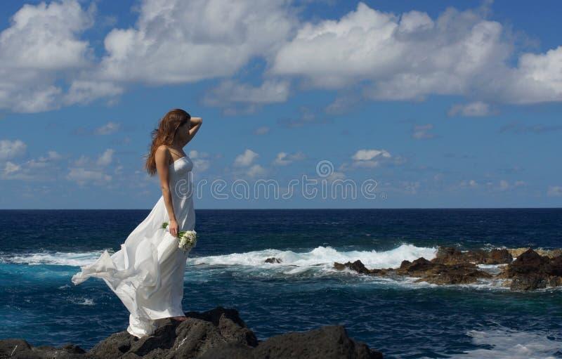 Młoda narzeczona w ślubnej sukni pozyci na skałach na dennym brzeg, Sao Miguel wyspa, Azores obrazy stock