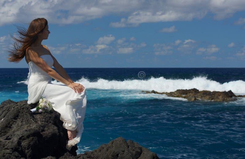 Młoda narzeczona w białym ślubnej sukni obsiadaniu na rockowym brzeg i patrzeć ocean na Sao Miguel wyspie, Azores obraz royalty free