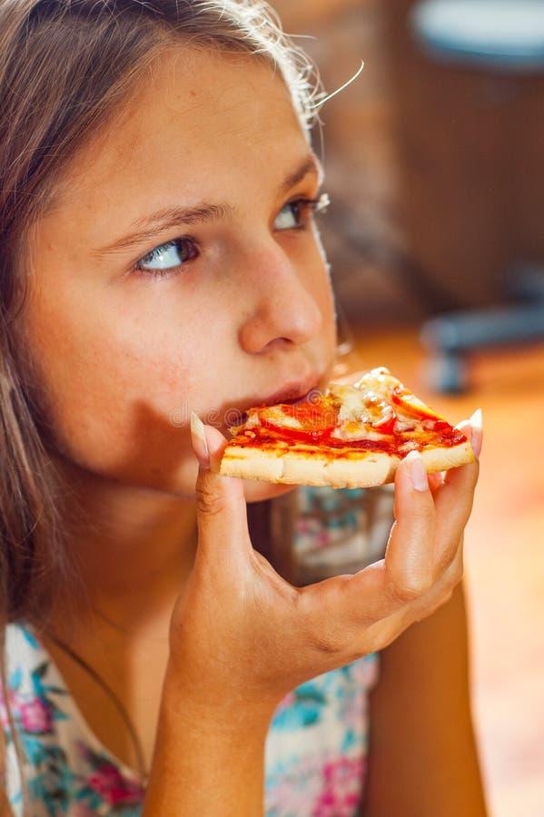 Młoda nastolatek brunetki dziewczyna je kawałek pizza fotografia stock