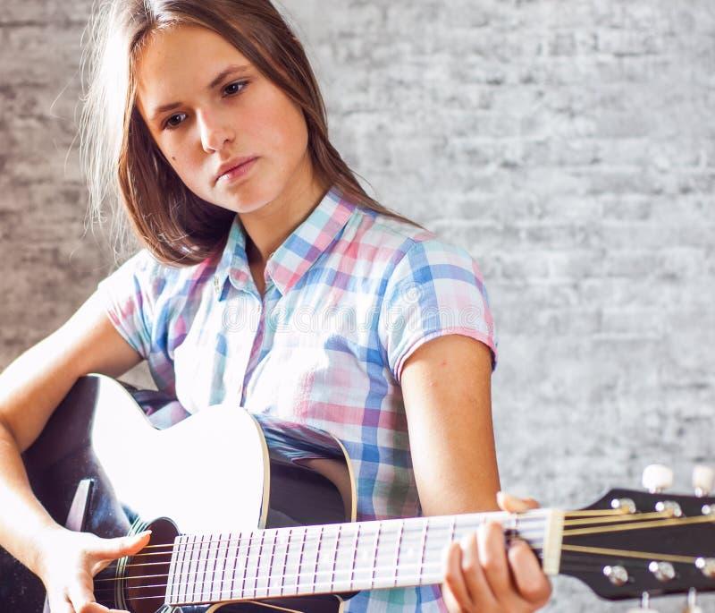 Młoda nastolatek brunetki dziewczyna z długie włosy bawić się czarną gitarę akustyczną na szarość izoluje tło obraz royalty free