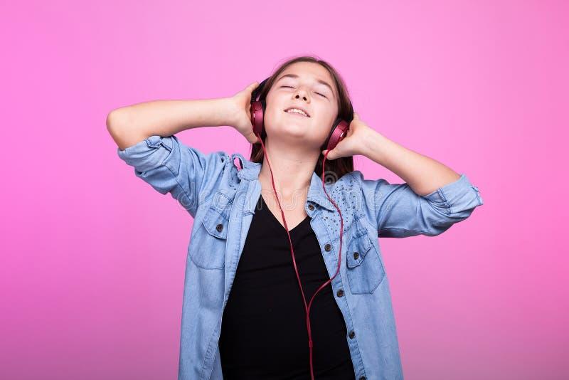 Młoda nastolatek dziewczyna cieszy się muzykę z hełmofonami na głowie fotografia royalty free