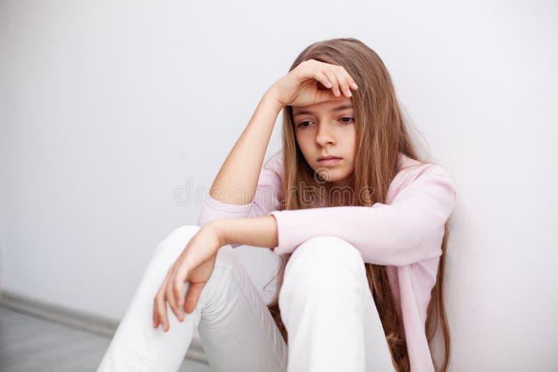 Młoda nastolatek dziewczyna ma zawał serca - siedzący na podłoga obok obraz stock