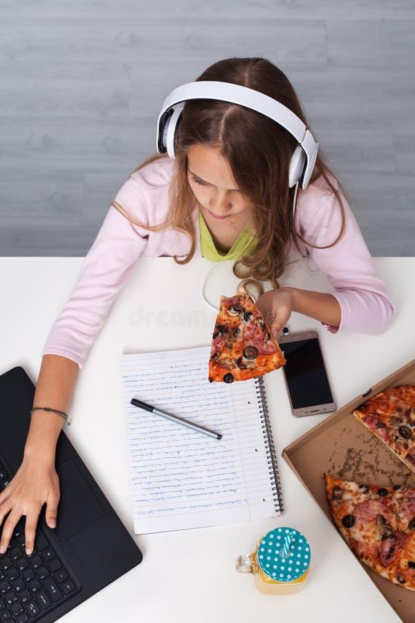 Młoda nastolatek dziewczyna pracuje na szkolnym projekcie - mieć przekąskę obrazy royalty free