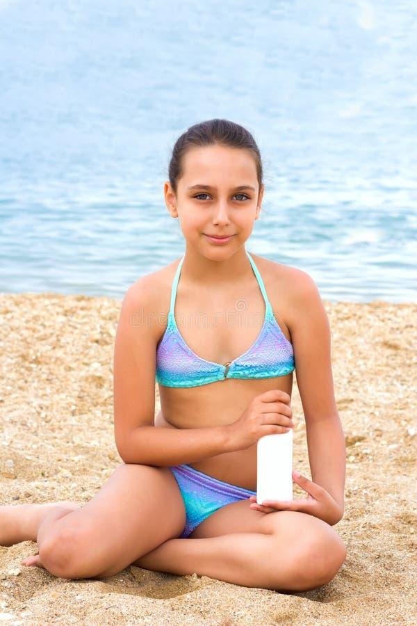 Młoda nastolatek dziewczyny lata morza plaży sunblock sunscreen śmietanka zdjęcia royalty free