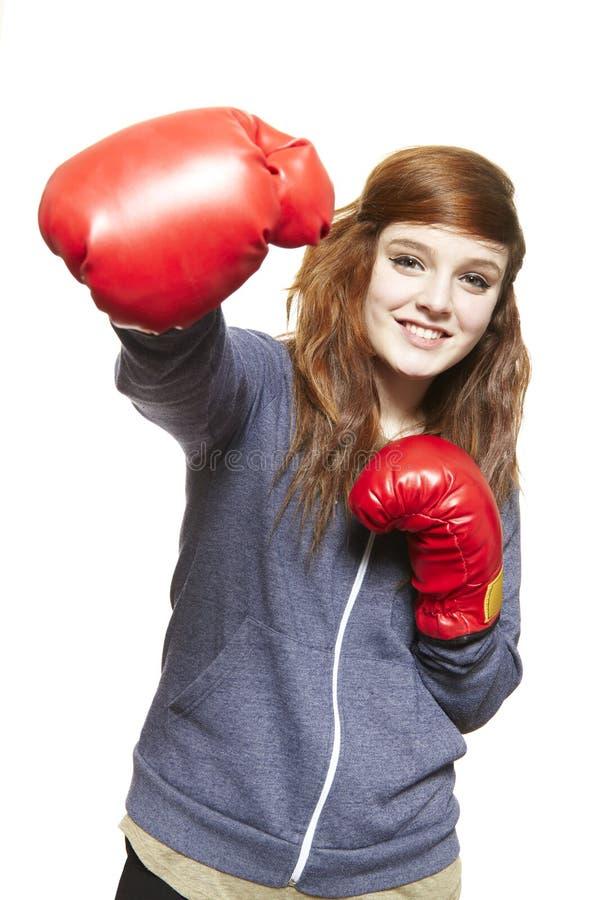 Młoda nastoletnia dziewczyna jest ubranym bokserskich rękawiczek ono uśmiecha się zdjęcia stock