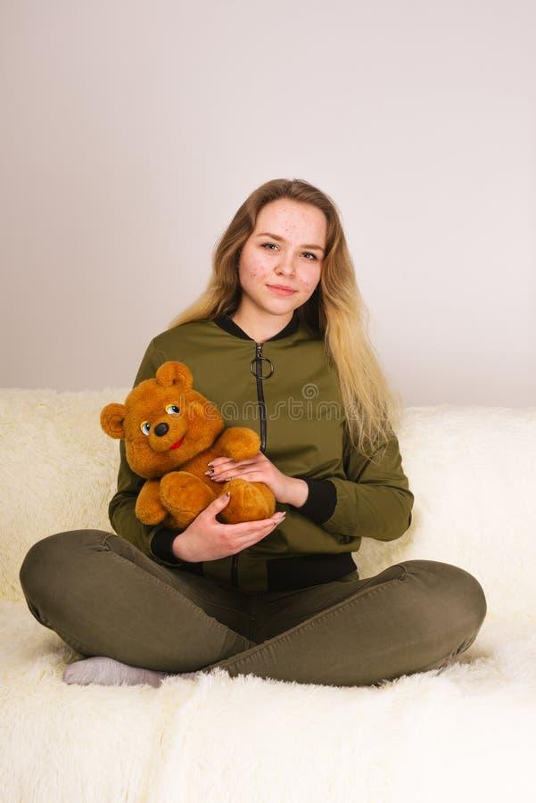 Młoda nastoletnia dziewczyna z trądzik twarzy obsiadaniem na kanapy i mienia misiu zdjęcia stock