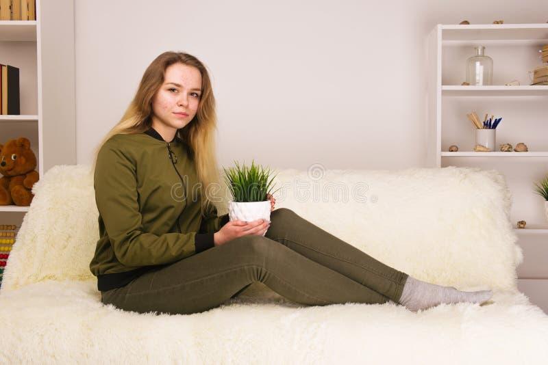 Młoda nastoletnia dziewczyna z trądzik twarzy obsiadaniem na kanapy i mienia zielonym houseplant obrazy stock