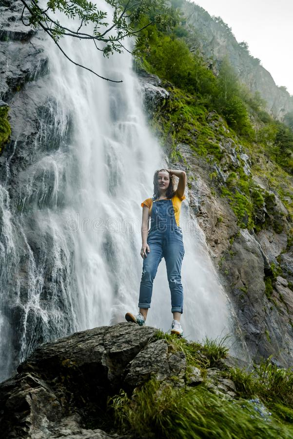 Młoda nastoletniej dziewczyny pozycja na dużej kamiennej pobliskiej siklawie zdjęcia stock