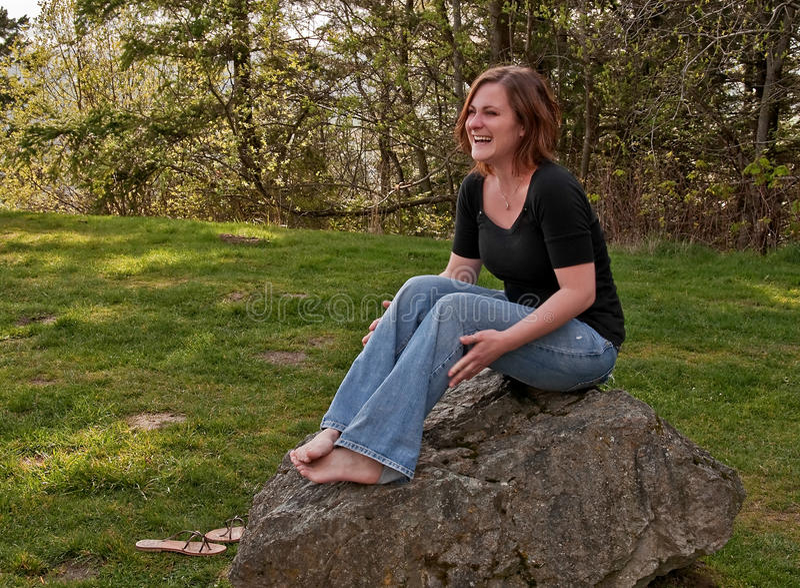 Młoda Naturalna Przyglądająca kobieta Laughin Podczas gdy Siedzący na Rockowym Barefo obraz stock