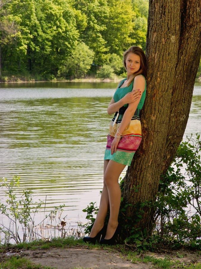 Młoda nikła ładna dziewczyna w drzewnym cieniu obrazy stock
