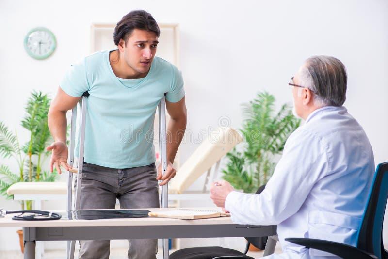 Młoda noga ranił męskiego pacjenta odwiedza starą lekarkę fotografia stock