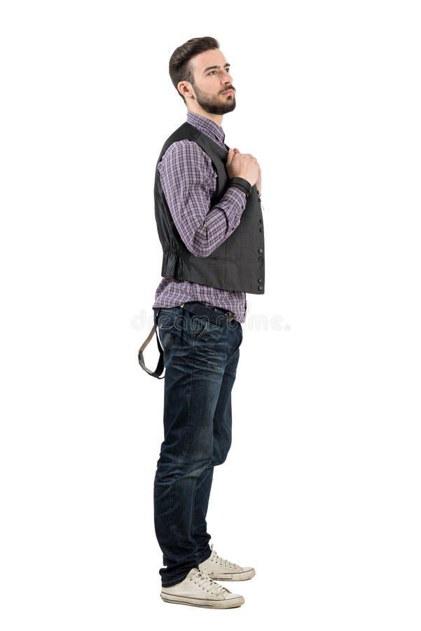Młoda nowożytna brodata modnisia mienia kamizelka patrzeje odległość zdjęcia royalty free