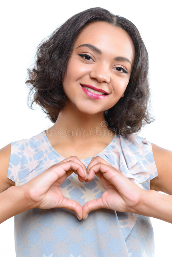 Młoda oliwkowa dziewczyna pokazuje sercu z ona palce obraz royalty free