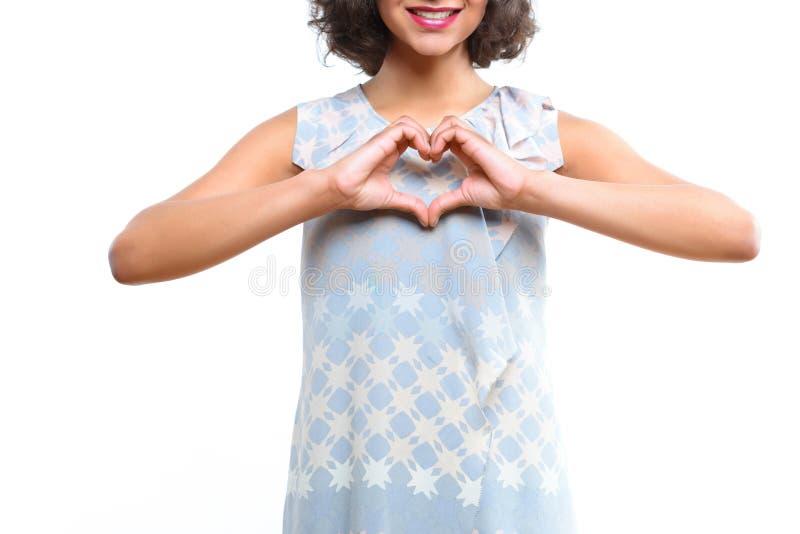 Młoda oliwkowa dziewczyna pokazuje sercu z ona palce fotografia royalty free