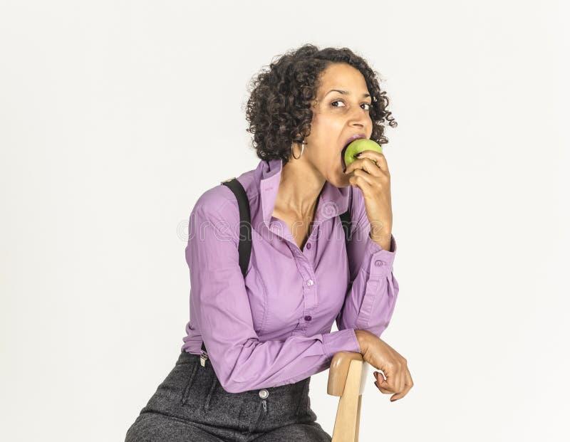 Młoda oliwkowa kobieta w garniturze je jabłka obraz stock