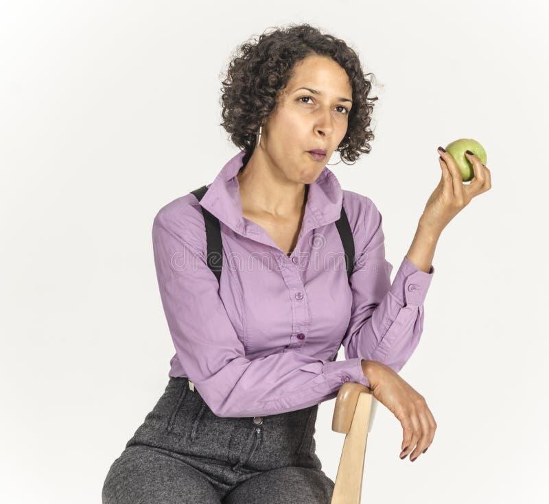 Młoda oliwkowa kobieta w garniturze je jabłka obrazy stock