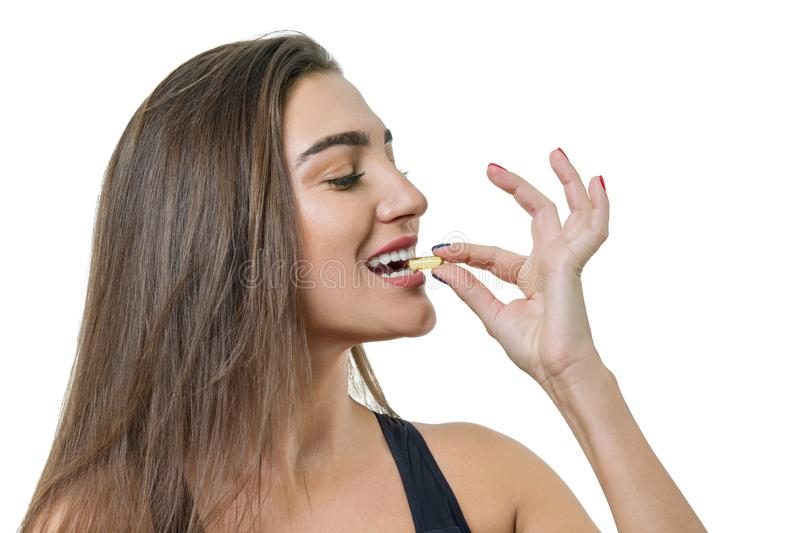 Młoda ono uśmiecha się piękna zdrowa kobieta w sportswear z witaminy d, E, A rybiego oleju omega-3 kapsuły na białym odosobnionym obrazy stock