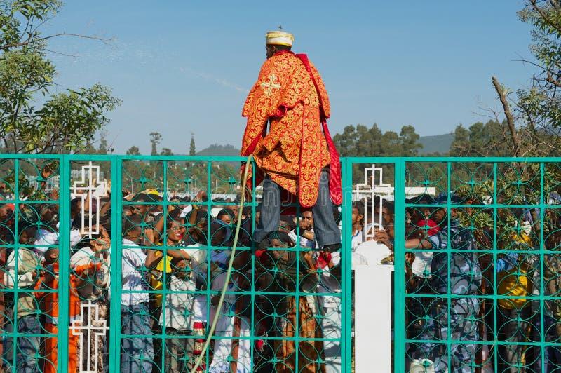 Młoda Ortodoksalna księży pluśnięć woda w tłumu świętuje Timkat festiwal religijnego w Addis Ababa, Etiopia obrazy stock