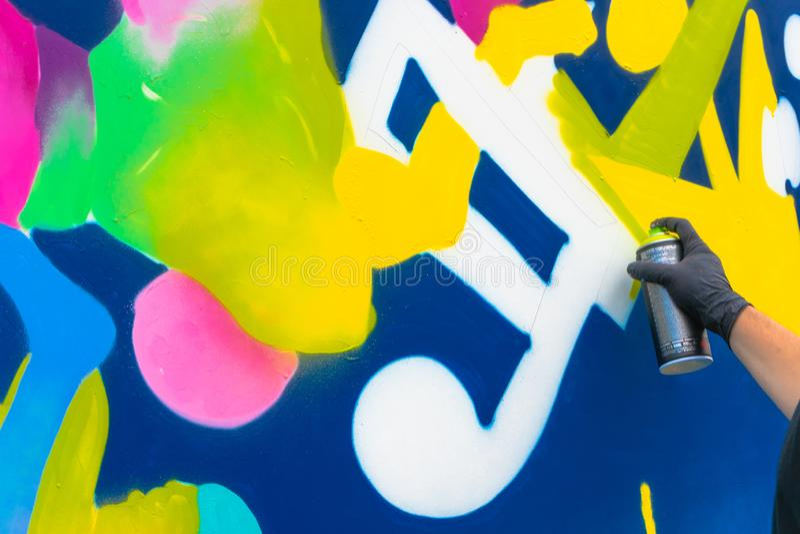 Młoda osoba rysunek z kiściami - graffiti artysty obraz z aerosolowymi kolor puszkami na ścianie obrazy royalty free