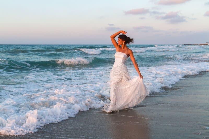 Młoda panna młoda cieszy się samotnego spacer na plaży przy półmrokiem fotografia stock