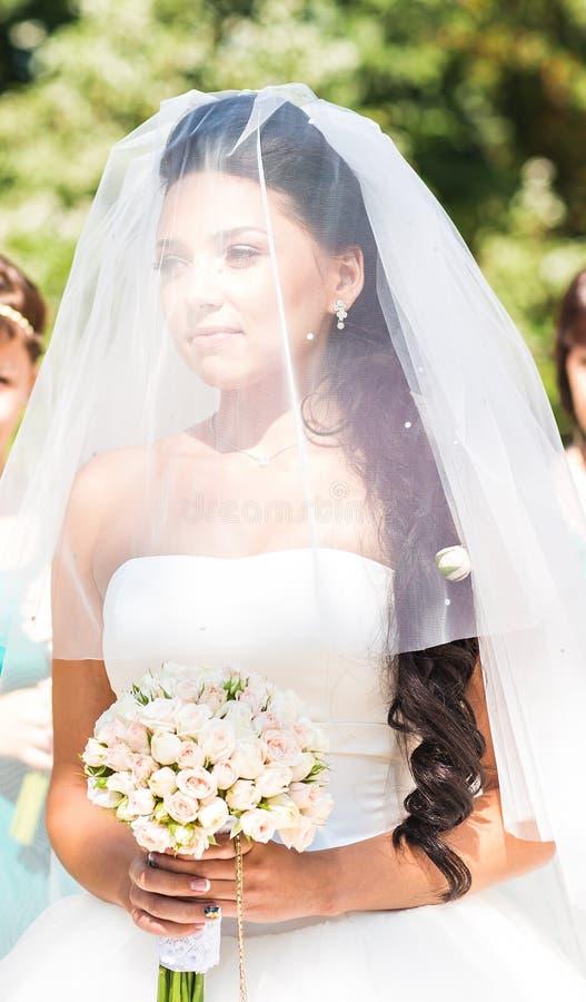Młoda panna młoda w ślubnej sukni i przesłony mienia bukiecie obrazy royalty free