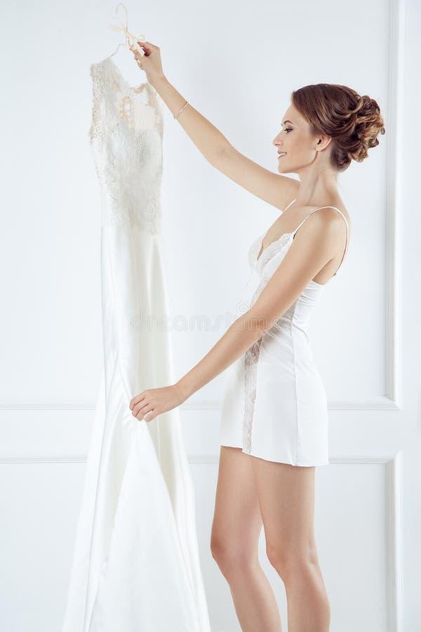 Młoda panna młoda trzyma elegancką ślubną suknię w białym pokoju obraz royalty free