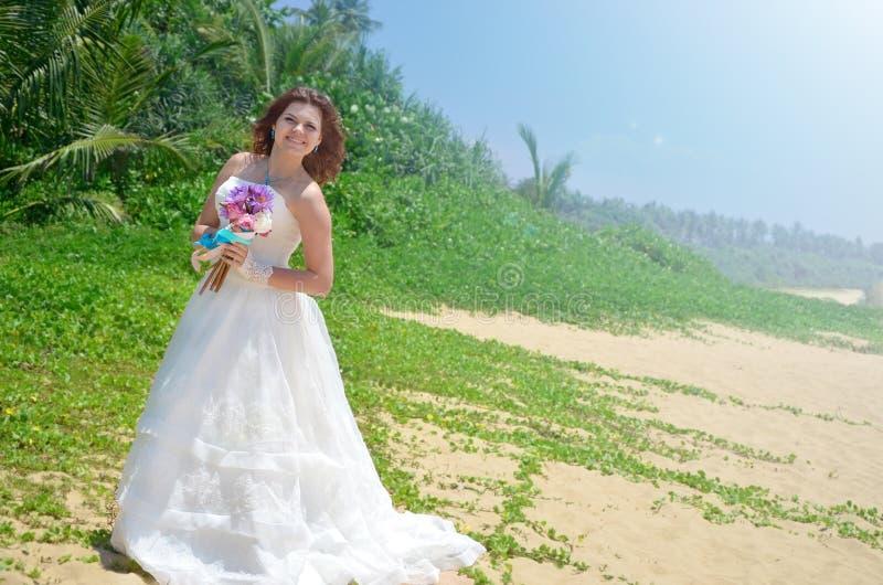 Młoda panna młoda w białej powiewnej sukni stoi z bukietem lotosy dziewczyna ono uśmiecha się na tropikalnej plaży na wyspie zdjęcia royalty free
