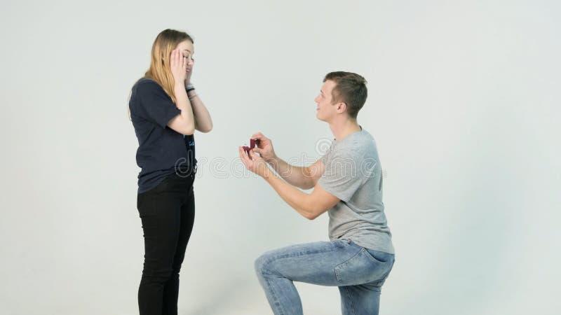 Młoda para ładna dziewczyna z długie włosy i przystojnym młodego człowieka obsiadaniem na kolanach robi propozyci na białym tle zdjęcie royalty free