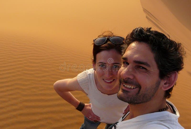 Młoda para bierze jaźń obrazek wierzchołek Wielka piasek diuna w czerwonym wydmowym morzu erg Chebbi podczas gdy wspinający się,  obrazy stock
