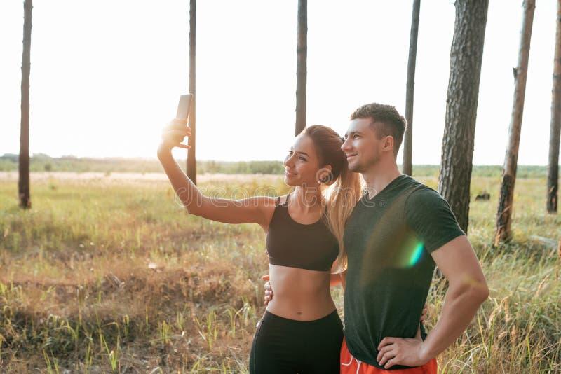 Młoda para, mężczyzna i kobieta, lato park, fotografujemy na telefonie, szczęśliwy ono uśmiecha się bawimy się, przed jogging, obraz stock