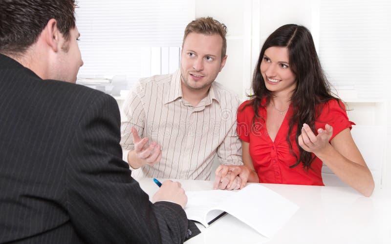 Młoda para małżeńska przy biurkiem w biznesowym spotkaniu obrazy stock