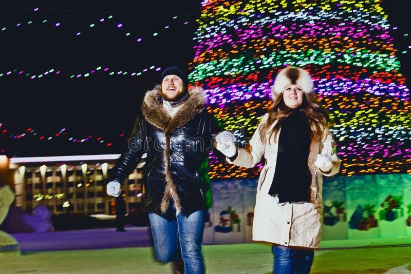 Młoda para w miłości runnung przy Bożenarodzeniową ulicą zdjęcie royalty free