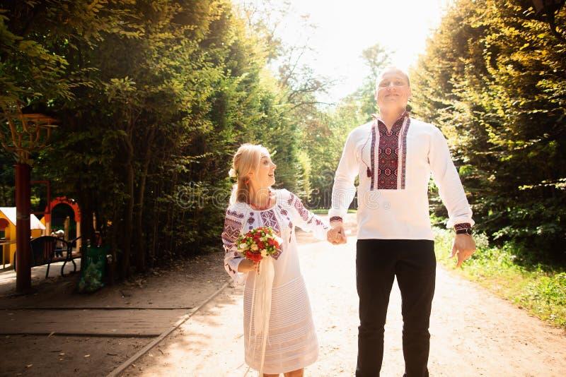 Młoda para w tradycyjnym Ukraińskim ubraniowym whith bukiecie cieszy się słonecznego dzień przy Stryisky parkiem w Lviv obrazy royalty free