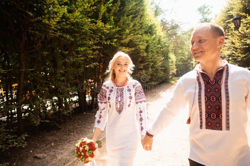 Młoda para w tradycyjnym Ukraińskim ubraniowym whith bukiecie cieszy się słonecznego dzień przy Stryisky parkiem w Lviv obraz stock