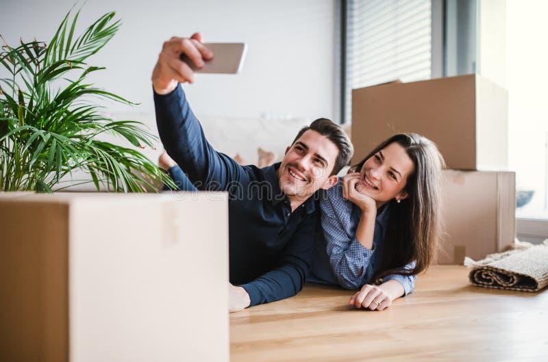 Młoda para z smartphone chodzeniem w nowym domu, bierze selfie obraz royalty free