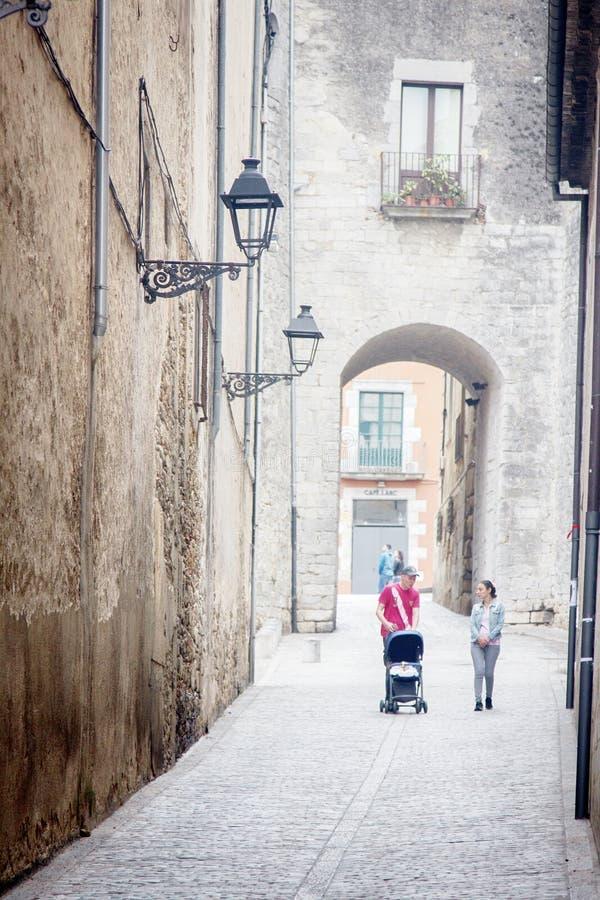 młoda para z wózkiem idąca w starym mieście Girona zdjęcie royalty free