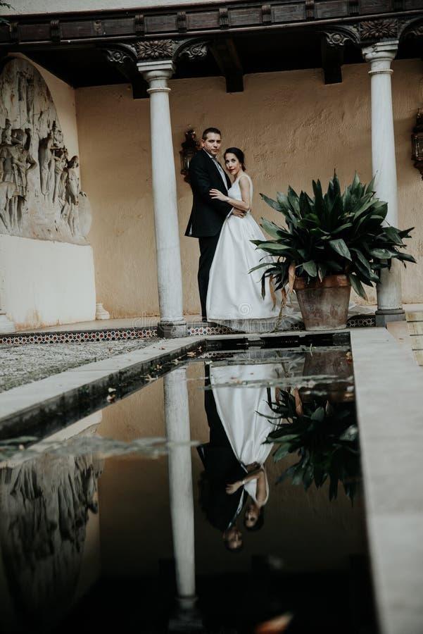Młoda pary panna młoda w bielu i fornal w czerni stoimy i odbijamy w wodzie zdjęcie royalty free