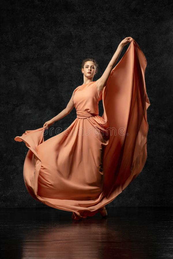 Młoda pełen wdzięku tancerz pozycja przeciw tłu czarna ściana ubierał w długiej brzoskwini kłębi się suknię fotografia stock