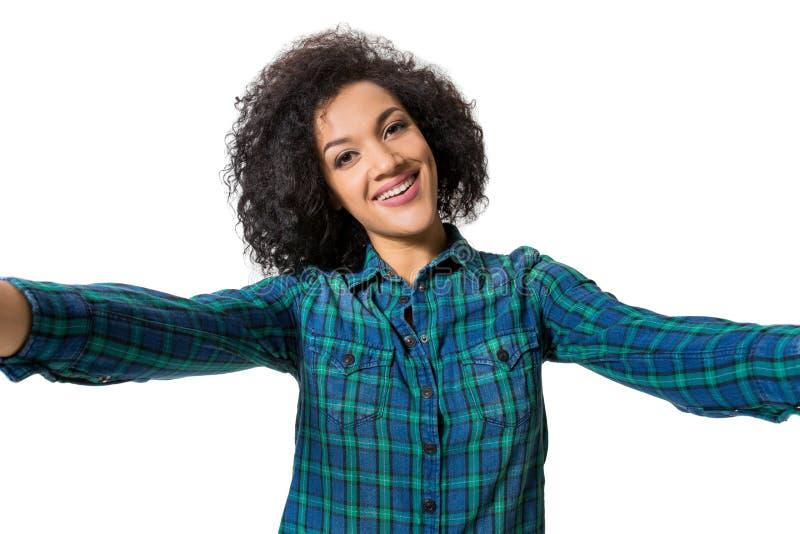 Młoda piękna amerykanin afrykańskiego pochodzenia kobieta robi jaźni przeciw białemu tłu w studiu obraz stock