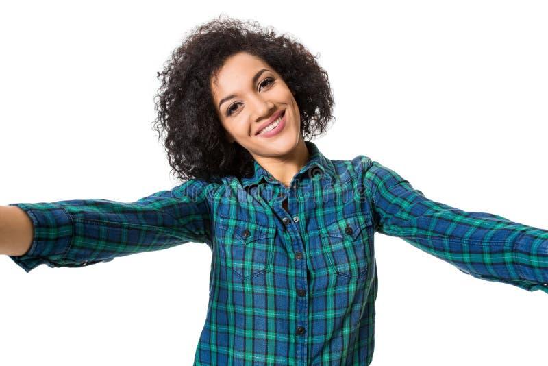 Młoda piękna amerykanin afrykańskiego pochodzenia kobieta robi jaźni przeciw białemu tłu w studiu fotografia stock