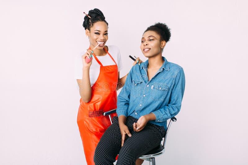 Młoda piękna amerykanin afrykańskiego pochodzenia kobieta stosuje fachowego makijaż Afrykańskim makijażu artysty Pracownianym kró obraz stock