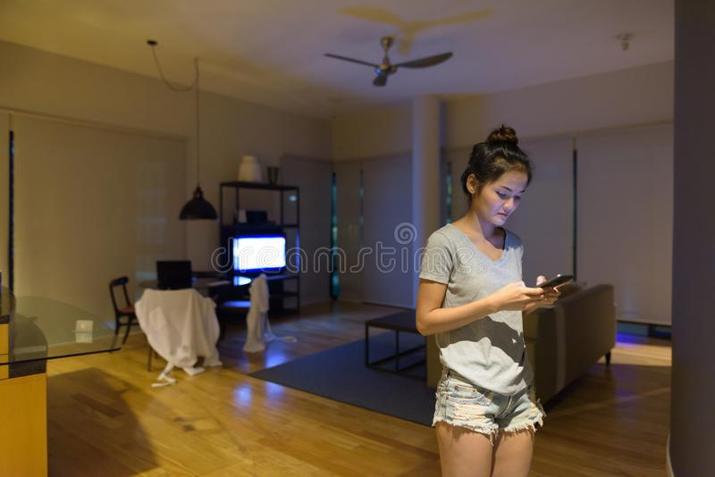 Młoda piękna Azjatycka kobieta relaksuje w żywym pokoju obraz royalty free