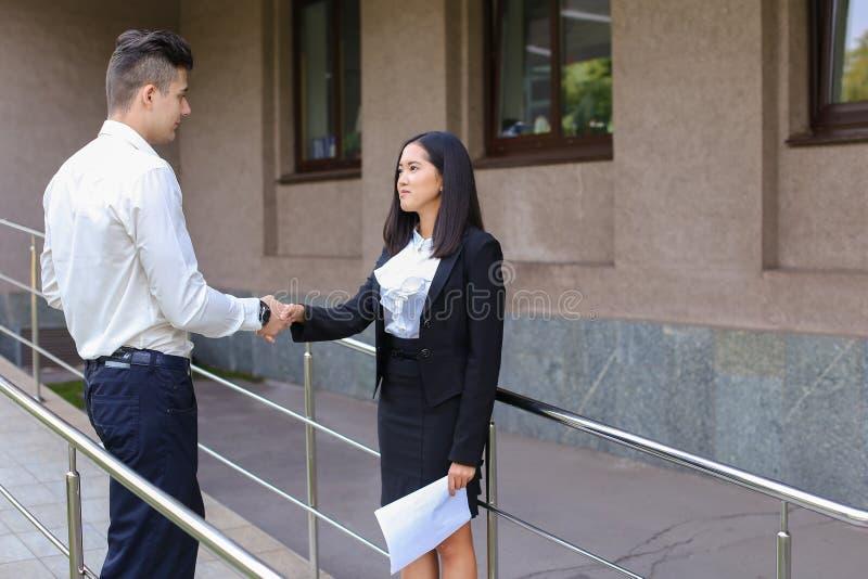 Młoda piękna azjatykcia biznesowa kobieta i caucasian męski spojrzenie przy zdjęcie royalty free