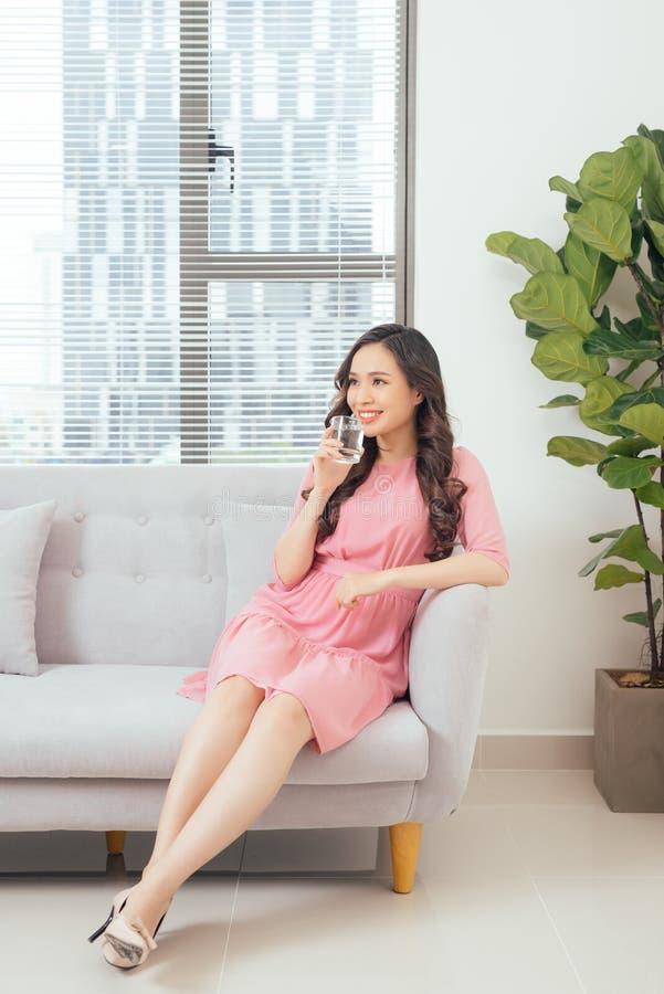 Młoda piękna azjatykcia kobieta relaksuje w kanapie z filiżanką czysty wa zdjęcia royalty free
